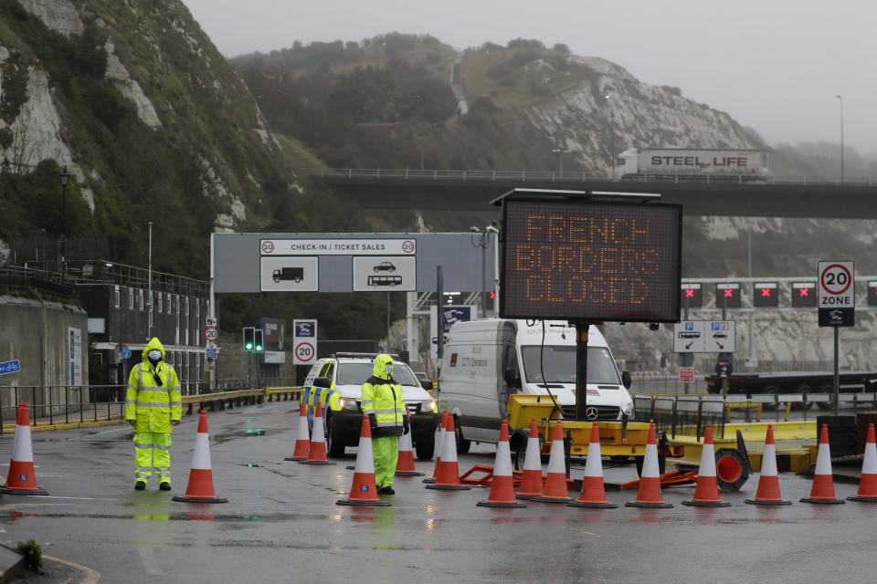 Security guard the entrance to the ferry terminal after the Port of Dover, England, Monday, Dec. 21, 2020, was closed and access to the Eurotunnel terminal suspended following the French government's announcement. France banned all travel from the UK for 48 hours from midnight Sun day, including trucks carrying freight through the tunnel under the English Channel or from the port of Dover on England's south coast. (AP Photo/Kirsty Wigglesworth)