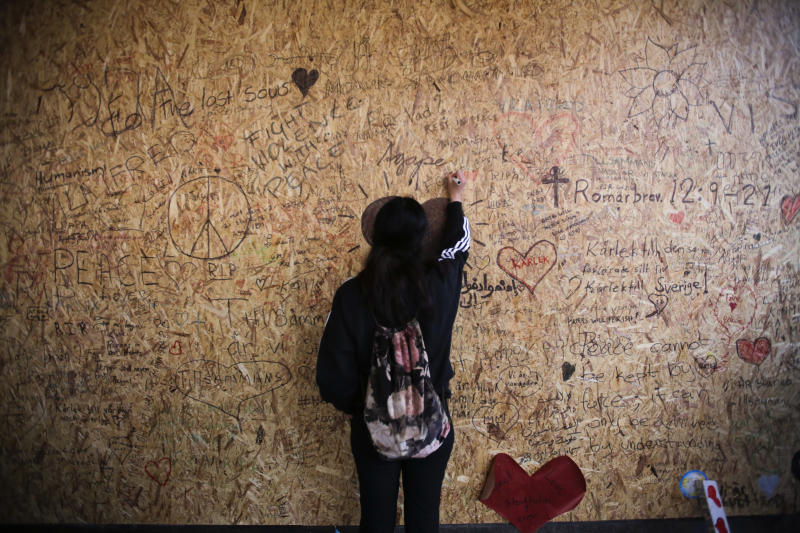 A woman writes a message on a wooden plank at the department store Ahlens in Stockholm, Sweden, Sunday, April 9, 2017. A hijacked truck was driven into a crowd of pedestrians and crashed into a department store on Friday. (AP Photo/Markus Schreiber)