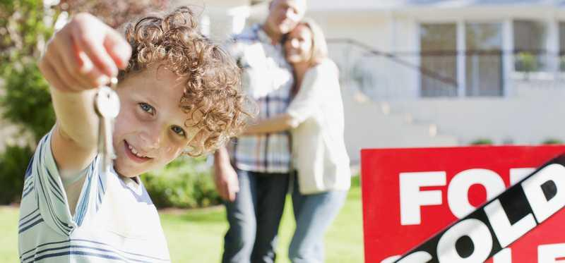 Kid holding house keys standing in front of parents and house with for sale/sold sign.