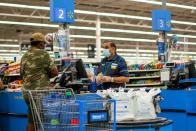 FILE PHOTO: FILE PHOTO: A worker and a shopper are seen wearing masks at a Walmart store, in North Brunswick, New Jersey
