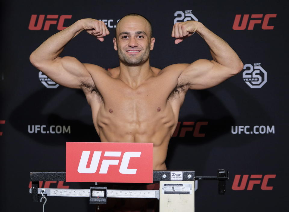FILE - UFC lightweight fighter Eddie Alvarez flexes during a weigh-in in Calgary, Alberta, in this Friday, July 27, 2018, file photo. Demetrious Johnson and Eddie Alvarez won UFC championships before leaving their native U.S. to pursue another title overseas. Their home fans will get to see their next fights in Singapore thanks to One Championship's new series of fight cards on TNT. (Jeff McIntosh/The Canadian Press via AP, File)