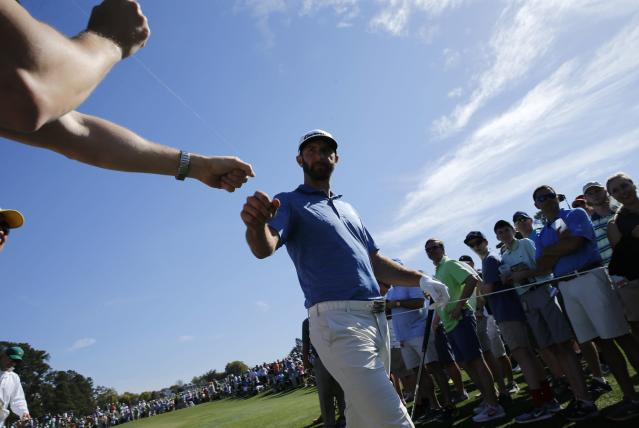 Dustin Johnson of the U.S. greets patrons between holes during practice for the 2018 Masters golf tournament at Augusta National Golf Club in Augusta, Georgia, U.S. April 2, 2018. REUTERS/Jonathan Ernst