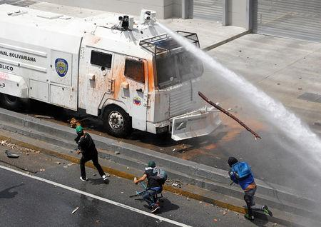 A police water cannon disperses demonstrators during an opposition rally in Caracas, Venezuela. REUTERS/Christian Veron