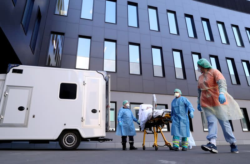 FILE PHOTO: Medical staff arrive with a patient affected by COVID-19 at CHC Montlegia hospital in Liege