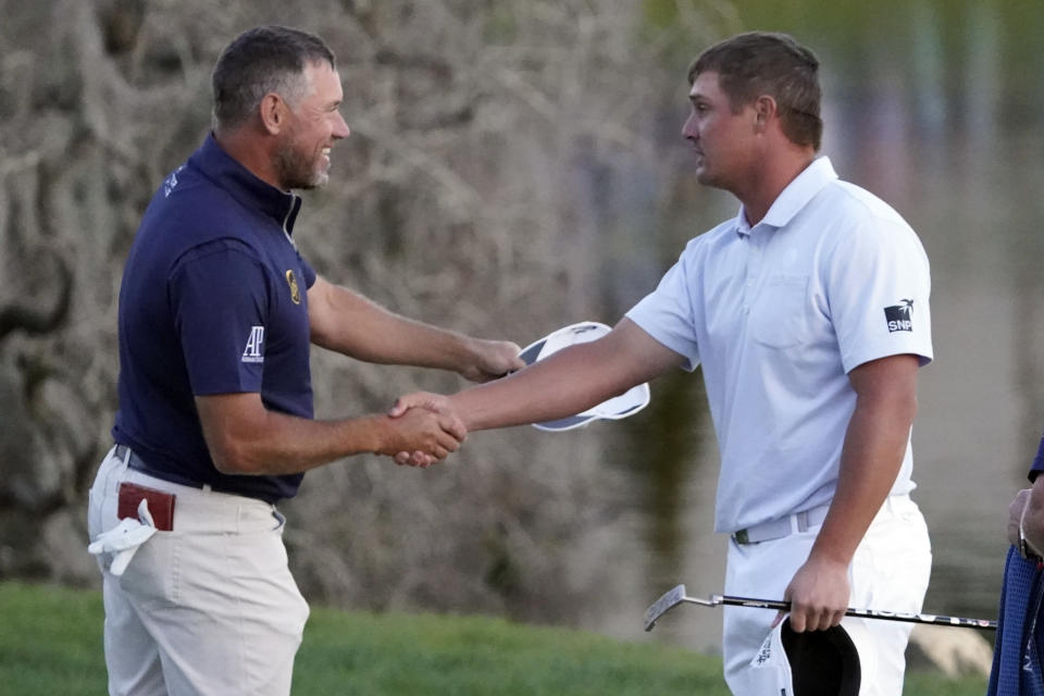 Lee Westwood, of England, and Bryson DeChambeau shake hands after they finished play in the Arnold Palmer Invitational golf tournament Sunday, March 7, 2021, in Orlando, Fla. DeChambeau won the tournament and Westwood finished second. (AP Photo/John Raoux)