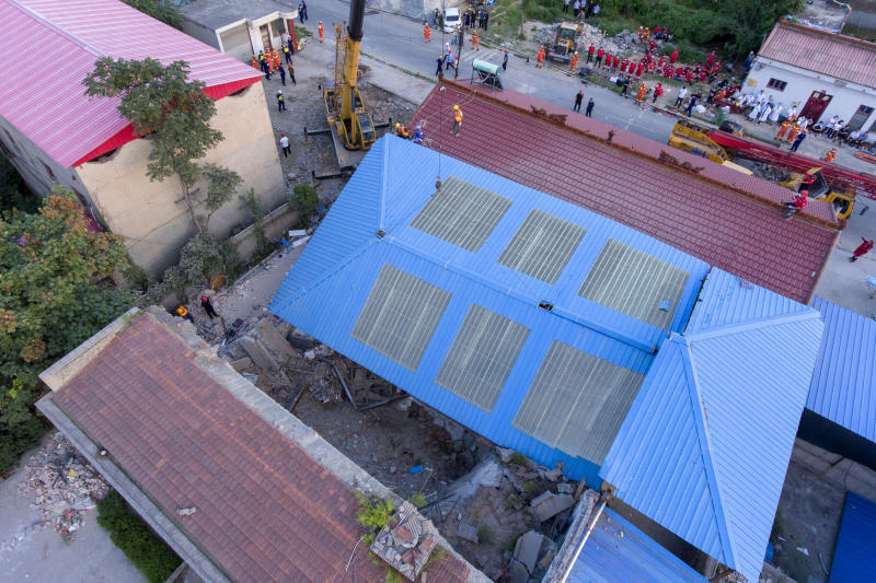 In this aerial photo released by Xinhua News Agency, rescue workers are seen near the site of a collapsed two-story restaurant in Xiangfen County of Linfen City, northern China's Shanxi Province, Saturday, Aug. 29, 2020. Rescue efforts ended at the two-story restaurant in the northern China village that collapsed during an 80th birthday celebration for a resident, leaving more than two dozen dead, authorities said Sunday. (Yang Chenguang/Xinhua via AP)