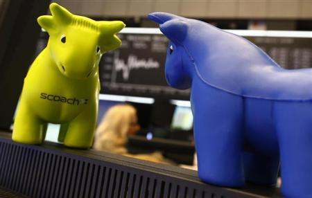 Small foam bull figures are seen in front of the German share price index DAX board at the stock exchange in Frankfurt