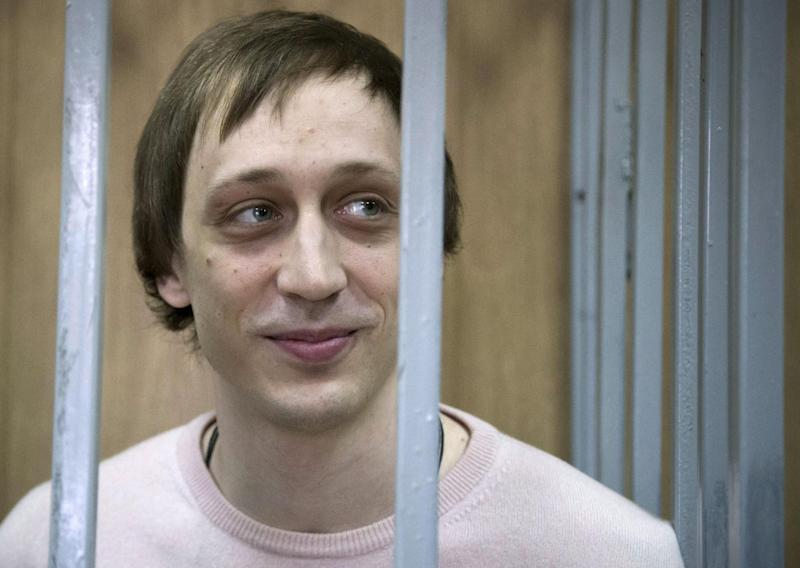 FILE - In this Tuesday Dec. 3, 2013 file photo, Pavel Dmitrichenko stands inside a barred enclosure at a courtroom in Moscow, Russia. A Moscow appeals court has lightened the prison sentences handed down to a Bolshoi dancer and two accomplices for their roles in an acid attack on the ballet's artistic director. Dancer Pavel Dmitrichenko was convicted in December of organizing the attack and sentenced to six years in prison. The Moscow City Court on Thursday, March 6, 2014, reduced his sentence by six months. (AP Photo/Alexander Zemlianichenko, file)
