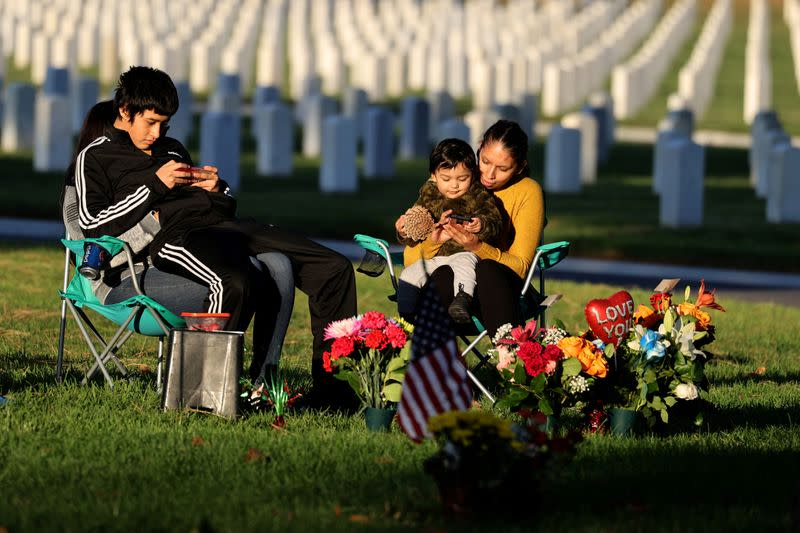 FILE PHOTO: Karina Hernandez, 35, sits with her one-year-old son Matthew, in front of the grave of her sister, U.S. Army Specialist Rocio Hernandez, at Los Angeles National Cemetery on Veterans' Day