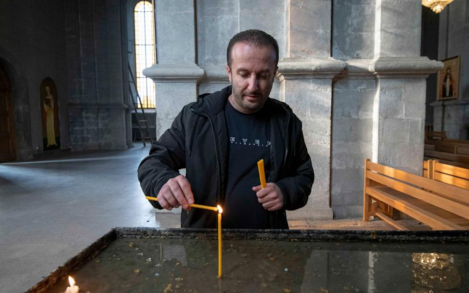 Armenian Diaspora Allen Sayadyan, 40, from Los Angeles, USA, lights some candles at the Holy Saviour Cathedral (Ghazanchetsots Cathedral ) in Shushi, the hill town 8 miles from Stepanakert in Nagorno-Karabakh. He left the country aged 10 years and moved with his wife and son back to Armenia three weeks ago. He is willing now to fight for Nagorno-Karabakh - Julian Simmonds
