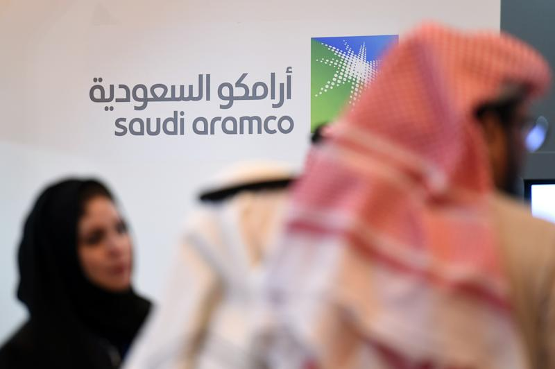 Saudi and Foreign investors stand in front of the logo of Saudi state oil giant Aramco. Photo: FAYEZ NURELDINE/AFP/Getty Images