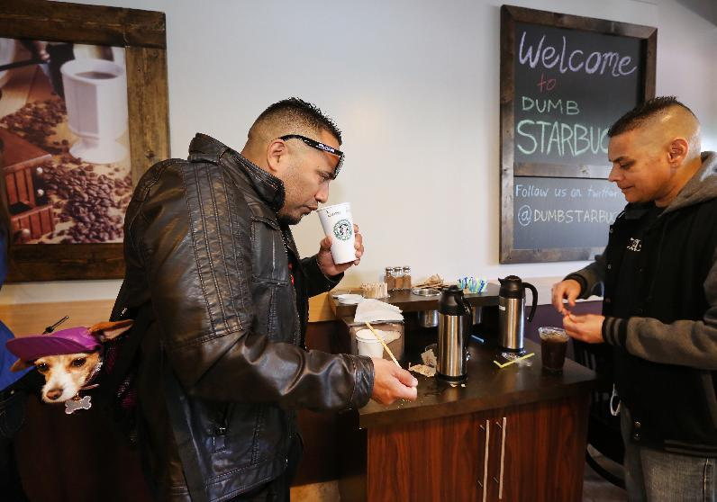 """Anthony Solis, left, and Tony Gonzalez prepare their coffee at the Dumb Starbucks coffee shop in Los Angeles Monday, Feb. 10, 2014. The store resembles a Starbucks with a green awning and mermaid logo, but with the word """"Dumb"""" attached above the Starbucks sign. Spokeswoman Laurel Harper says the store is not affiliated with Starbucks and, despite the humor, the store cannot use the Starbucks name. (AP Photo/Damian Dovarganes)"""