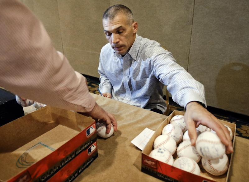 New York Yankees manager Joe Girardi signs baseballs at the baseball winter meetings on Tuesday, Dec. 4, 2012, in Nashville, Tenn. (AP Photo/Mark Humphrey)