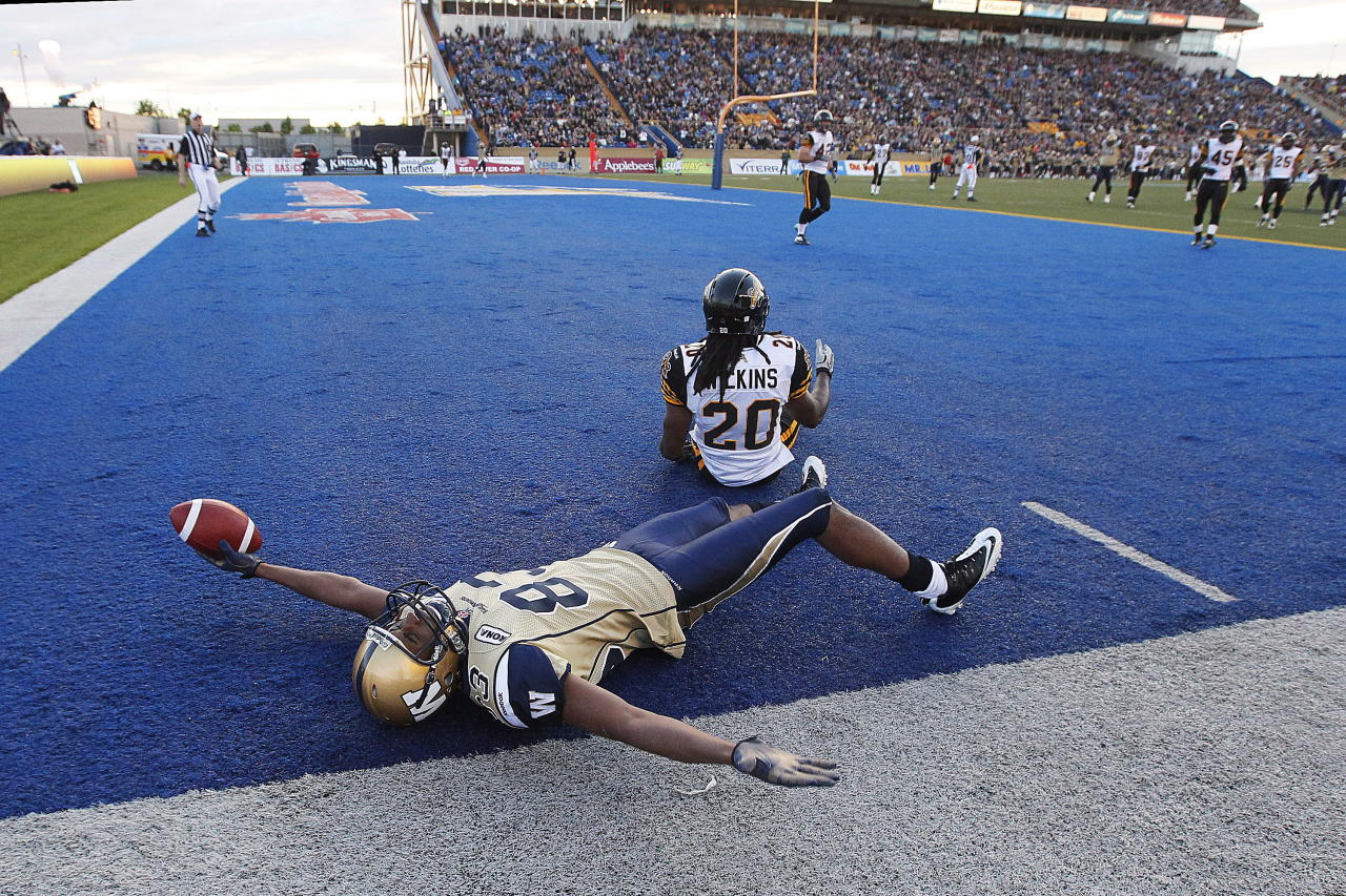 Winnipeg Blue Bombers' Doug Pierce (83) celebrates his touchdown against Hamilton Tiger-Cats' Josh Wilkins (20) during the second half of their pre-season CFL game in Winnipeg Wednesday, June 20, 2012. THE CANADIAN PRESS/John Woods