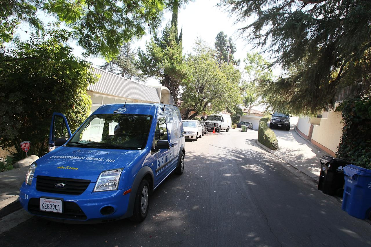 LOS ANGELES, CA - SEPTEMBER 27:  News vans are seen near the the building (R) where actor Johnny Lewis was found dead on September 27, 2012 in Los Angeles, California.  Lewis was found dead September 26, 2012 after apparently falling from the roof of the building he lived in.  He is also a suspect in the death of a woman who is thought to have been his landlord and was found dead inside the house.  (Photo by David Livingston/Getty Images)