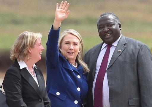 Virginia Blaser (L), Chargé d'Affaires at the US Embassy in Uganda, and Uganda's Foreign Minister Okello Oryem (R) welcome US Secretary of State Hilary Clinton. She paid tribute to a Ugandan human rights coalition working for gay rights, hours after a brief stop in Juba where she called for a compromise deal between the rival two Sudans