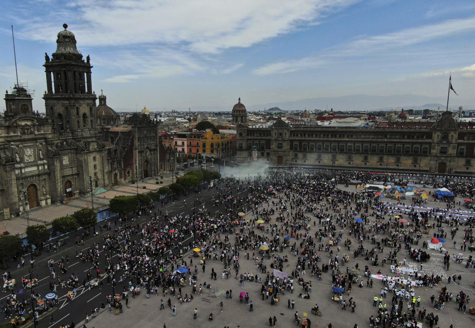 A plume from a fire extinguisher fired by the police to disperse demonstrators rises outside Mexico's Presidential Palace during a march commemorating International Women's Day in Mexico City, Monday, March 8, 2021. (AP Photo/Fernando Llano)