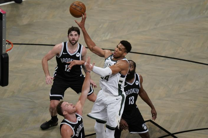 Milwaukee Bucks' Giannis Antetokounmpo (34) passes the ball away from Brooklyn Nets' Blake Griffin (2), James Harden (13) and Joe Harris (12) during the second half of Game 7 of a second-round NBA basketball playoff series Saturday, June 19, 2021, in New York. (AP Photo/Frank Franklin II)