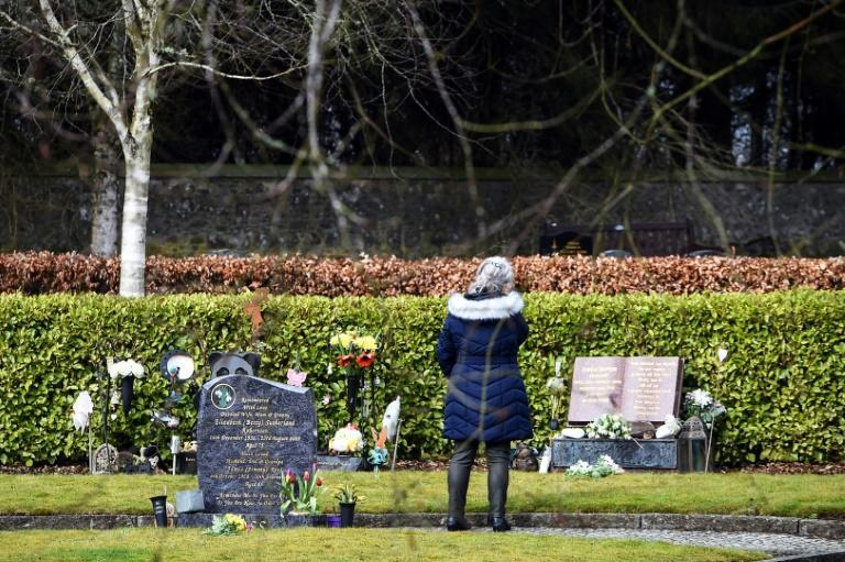 A woman stands at the gravestone of teacher Gwen Mayor in the memorial garden where the victims of the Dunblane school shooting are buried