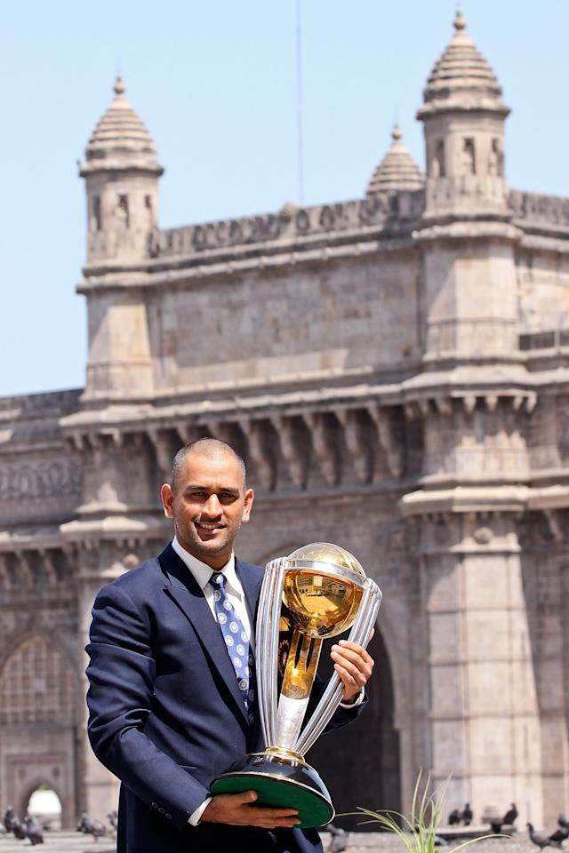 MUMBAI, INDIA - APRIL 03:  India's cricket team captain Mahendra Singh Dhoni poses with the  ICC Cricket World Cup Trophy, with the Gateway of India in the backdrop, during a photo call at the Taj Palace Hotel on April 3, 2011 in Mumbai, India.  (Photo by Ritam Banerjee/Getty Images)