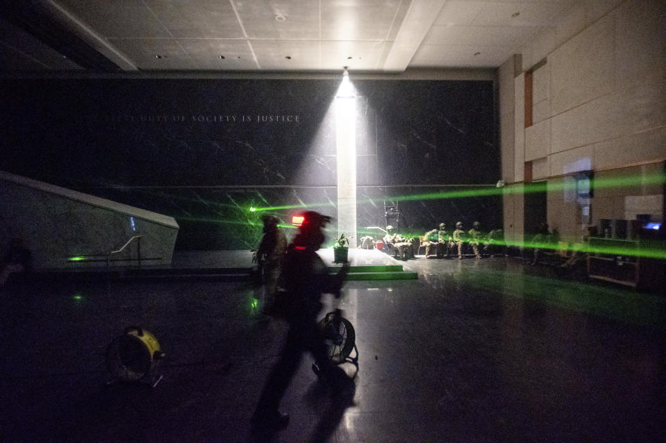 Green lines cast by protesters' laser pointers cross the darkened lobby of the Mark O. Hatfield U.S. Courthouse as federal officers wait for a possible skirmish with demonstrators Friday, July 24, 2020, in Portland, Ore. The beams, which can damage eyes, are routinely aimed at U.S. Marshals guarding the courthouse. On the streets of Portland, a strange armed conflict unfolds night after night. It is raw, frightening and painful on both sides of an iron fence separating the protesters on the outside and federal agents guarding a courthouse inside. This weekend, journalists for The Associated Press spent the weekend both outside, with the protesters, and inside the courthouse, with the federal agents, documenting the fight that has become an unlikely centerpiece of the protest movement gripping America. (AP Photo/Noah Berger)