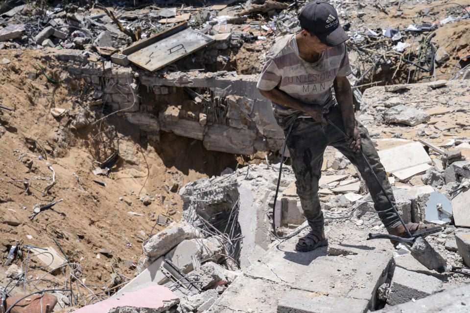 A worker tugs on an electrical cable as people gather reclaimable debris from the site of a building previously destroyed by an airstrike prior to a cease-fire reached after an 11-day war between Gaza's Hamas rulers and Israel, in Gaza City, Saturday, May 22, 2021. (AP Photo/John Minchillo)
