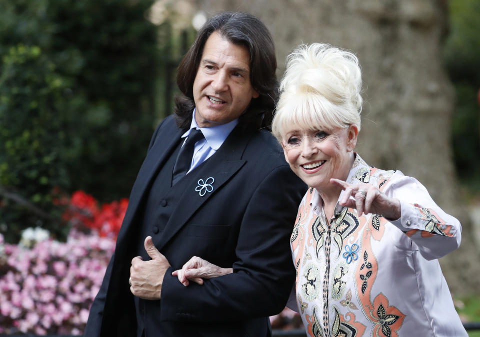 British actress Barbra Windsor waves at the media as she arrives with her husband Scott Mitchell, in Downing Street, London, Monday, Sept. 2, 2019, to promote Dementia Care. (AP Photo/Alastair Grant)