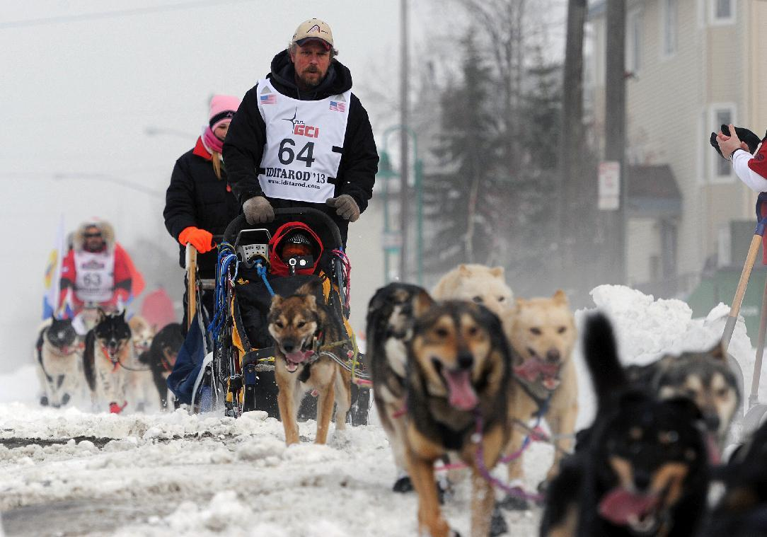 Matt Giblin (64) leads Mikhail Telpin (63) of Russia, as they near the Cordova Street hill during the ceremonial start of the ceremonial start of the Iditarod Trail Sled Dog Race on Saturday, March 2, 2013, in Anchorage, Alaska. The competitive portion of the 1,000-mile race is scheduled to begin Sunday in Willow, Alaska. (AP Photo/Anchorage Daily News, )