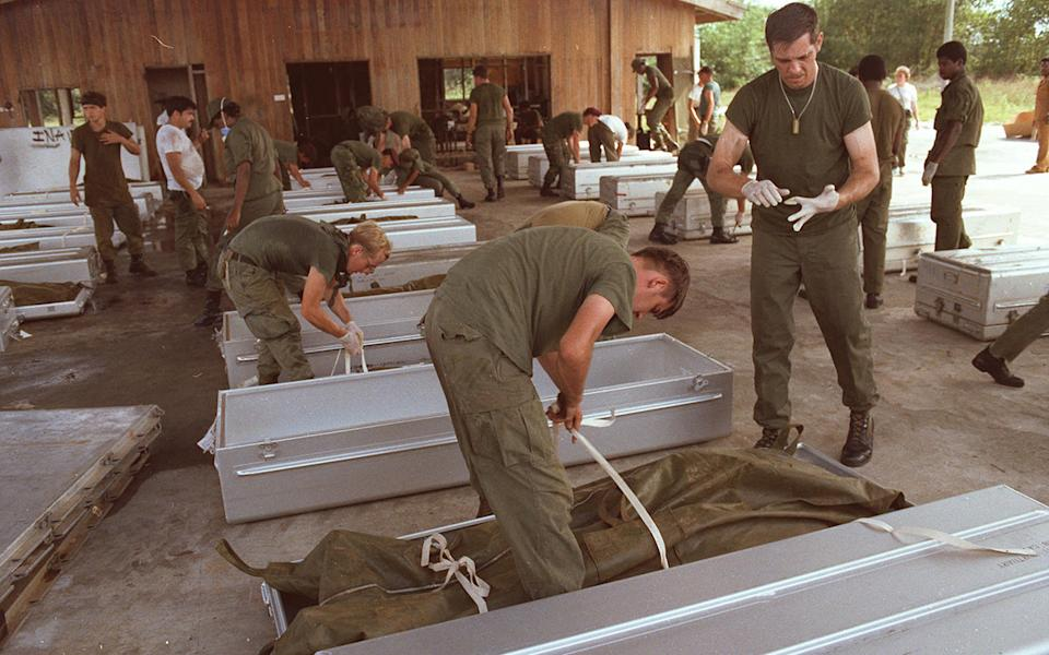 Soldiers clean up the bodies after the mass suicide at Jonestown. Source: Getty Images