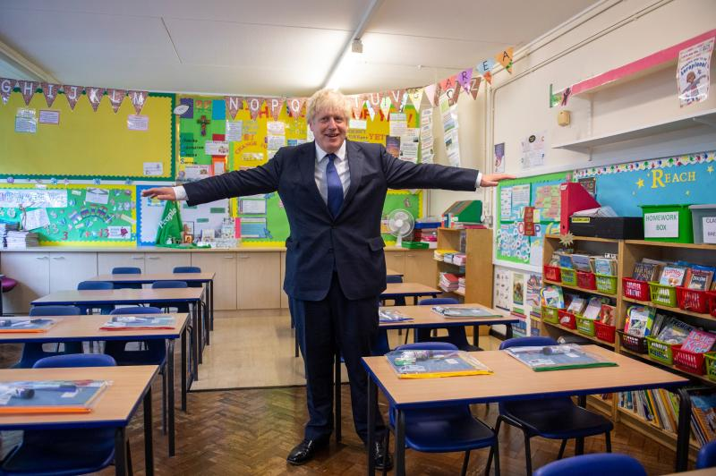 Britain's Prime Minister Boris Johnson poses with his arms out-stretched in a classroom as he visits St Joseph's Catholic Primary School in Upminster, east London, on August 10, 2020 to see preparedness plans implemented ahead of the start of the new school year as a response to the novel coronavirus pandemic. (Photo by Lucy YOUNG / POOL / AFP) (Photo by LUCY YOUNG/POOL/AFP via Getty Images)