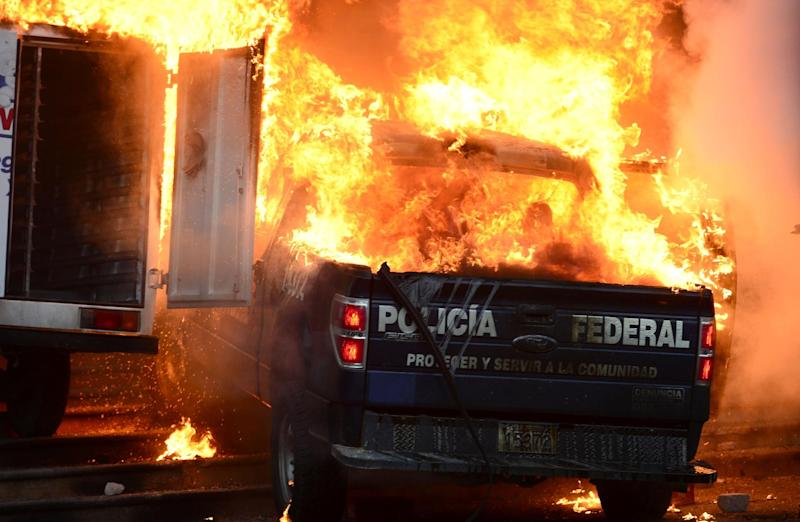 More than 300 students, many wearing masks, descended on the Guerrero state building in Chilpancingo, threw rocks at its windows and burned around 10 vehicles, including trucks and a federal police vehicle (AFP Photo/Ronaldo Schemidt)