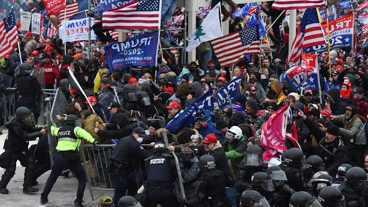Trump supporters clash with police and security forces as they push barricades to storm the US Capitol in Washington D.C on January 6, 2021. (Roberto Schmidt/AFP via Getty Images)