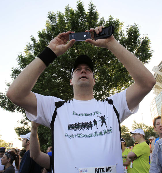 In this Sunday, May 20, 2012 photo, Congressman Tim Ryan takes a photo before running in the Cleveland Marathon, in Cleveland. In what's become a daily ritual, Ryan finds a quiet spot, closes his eyes, clears his mind and tries to tap into the eternal calm. Increasingly, people in settings beyond the serene yoga studio or contemplative nature path are engaging in the practice of mindfulness, a mental technique that dwells on breathing, periods of silence and concentration to keep one's thoughts in the present moment. (AP Photo/Tony Dejak)