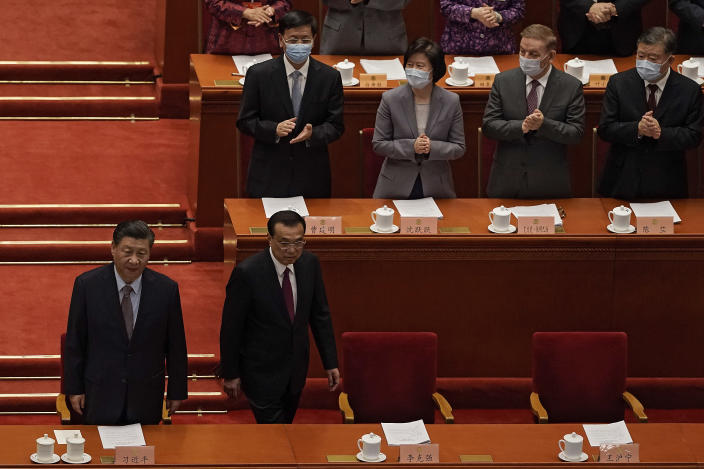 Delegates wearing face masks to help curb the spread of the coronavirus applaud as Chinese President Xi Jinping, left, and his Premier Li Keqiang arrive for the opening session of Chinese People's Political Consultative Conference (CPPCC) at the Great Hall of the People in Beijing, Thursday, March 4, 2021. (AP Photo/Andy Wong)