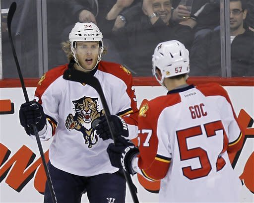 Florida Panthers' Kris Versteeg (32) celebrates with Marcel Goc (57) after scoring a goal during the first period of an NHL hockey game against the Winnipeg Jets in Winnipeg, Manitoba, Thursday, Nov. 10, 2011. (AP Photo/The Canadian Press, Trevor Hagan)