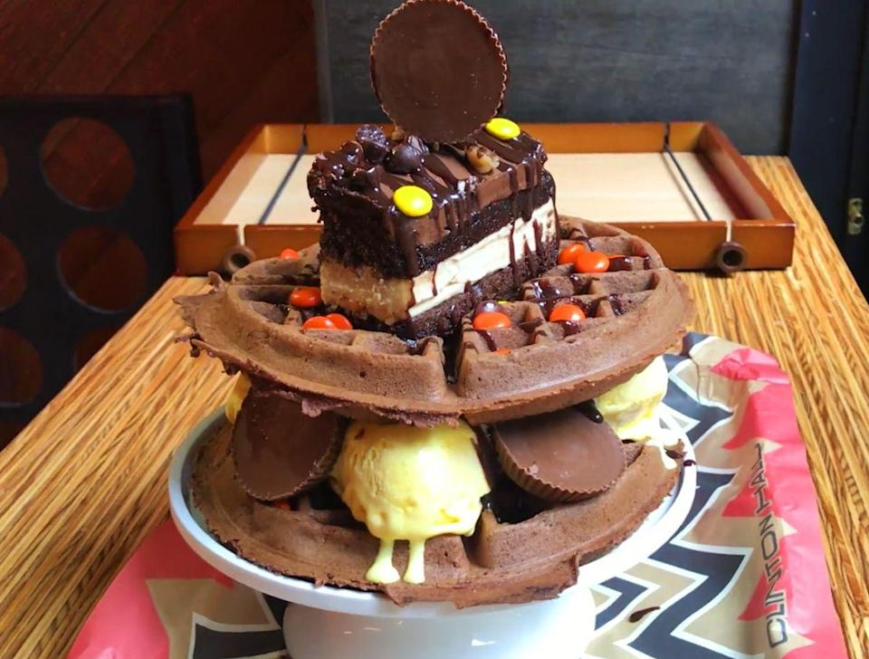 """<p>So Clinton Hall really blurred the line between breakfast and dessert here, but we really can't bring ourselves to care. We just want a fork. This is a <a rel=""""nofollow noopener"""" href=""""https://www.delish.com/restaurants/a23454930/chocolate-peanut-butter-waffle-tower-clinton-hall/"""" target=""""_blank"""" data-ylk=""""slk:tower of chocolate waffles"""" class=""""link rapid-noclick-resp"""">tower of chocolate waffles</a>, banana ice cream, Reese's candies, and a giant slice of cake.</p>"""
