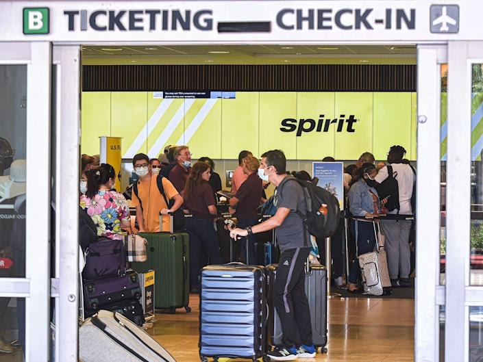 Passengers wait in line at the Spirit Airlines check-in counter at Orlando International Airport on the sixth day the airline has cancelled hundreds of flights.