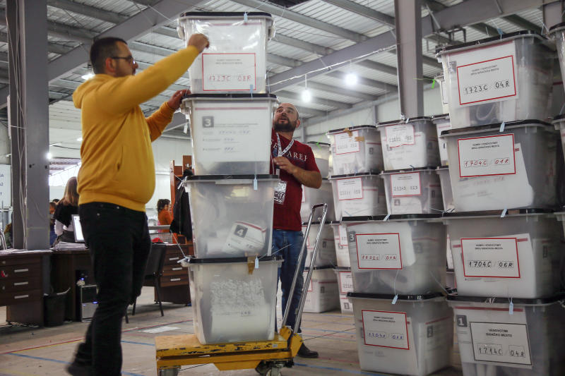 Workers carry ballot boxes at Central Election Committee counting center in Fushe Kosove, Kosovo on Monday, Oct. 7, 2019. Kosovo's opposition parties have won a snap election, overcoming the former independence fighters who have governed the country since its war 20 years ago. With 96% of the votes counted Monday the left-wing Movement for Self-Determination Party, or LVV, has 26% of the votes, one percentage point more than the conservative Democratic League of Kosovo, or LDK, also formerly in opposition. (AP Photo/Visar Kryeziu)