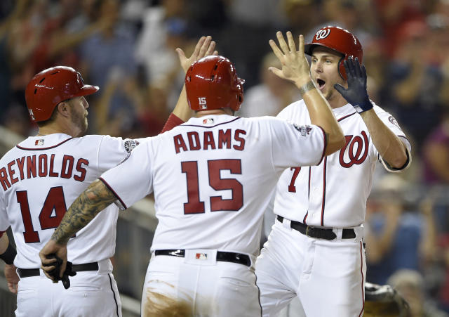 Washington Nationals' Trea Turner (7) celebrates his grand slam with Mark Reynolds (14) and Matt Adams (15) during the sixth inning of a baseball game against the Miami Marlins, Thursday, July 5, 2018, in Washington. The Nationals won 14-12. (AP Photo/Nick Wass)