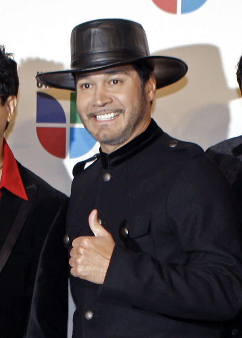 "FILE - This Nov. 13, 2008 file photo shows Oscar De La Rosa, lead singer for the Tejano group La Mafia, at the 9th annual Latin Grammy Awards in Houston. De La Rosa was knocked unconscious by a man in an unprovoked attack outside a Houston club on Monday, May 13, 2013. De La Rosa has facial cuts, eye damage and he lost two teeth.   La Mafia is considering whether to cancel any performances. The band, which formed in 1980 in Houston, won a Grammy in 2006 for the album, ""Nuevamente."" (AP Photo/LM Otero, file)"