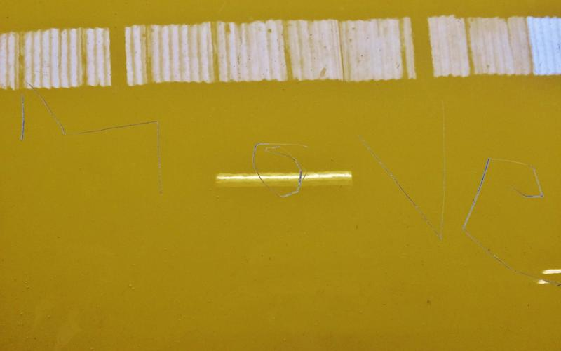 The word 'MOVE' was scratched into the bonnet of the bright yellow car - Credit: SWNS