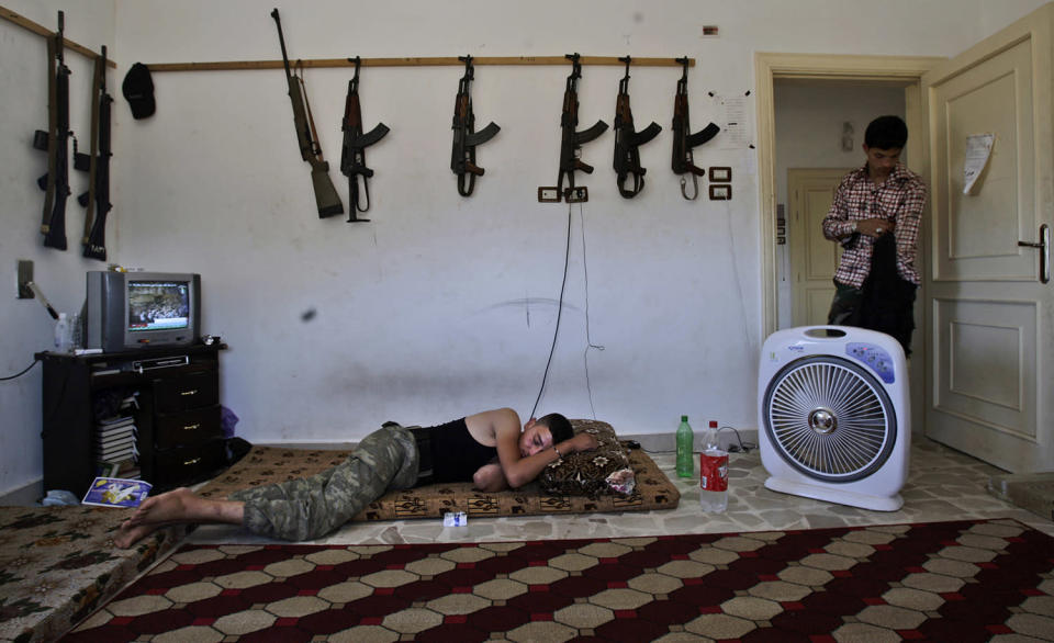 <p>A Syrian rebel, sleeps after returning back from fighting against Syrian army forces in Aleppo, at a rebel headquarters in Marea on the outskirts of Aleppo city, Syria, Aug. 26, 2012. (Photo: Muhammed Muheisen/AP) </p>