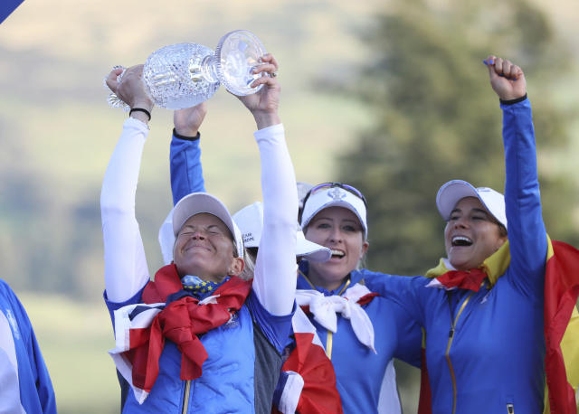Suzann Pettersen of Team Europe lifts the Solheim Cup as she celebrates with teammates after victory against the US at Gleneagles, Auchterarder, Scotland, Sunday, Sept. 15, 2019. (AP Photo/Peter Morrison)