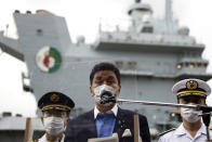 Japan's Defense Minister Nobuo Kishi, center, speaks to the members of the media after he inspected the British Royal Navy's HMS Queen Elizabeth aircraft carrier, back, at the U.S. naval base in Yokosuka, Kanagawa Prefecture, Japan Monday, Sept. 6, 2021. (Kiyoshi Ota/Pool Photo via AP)