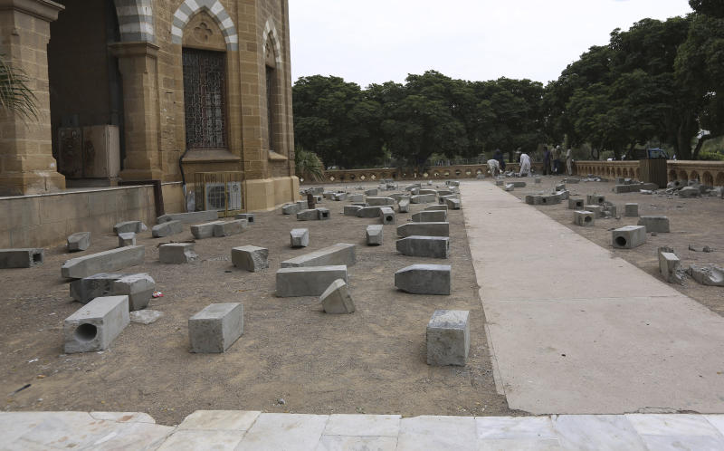 """Workers of Karachi Municipal Corporation remove an artwork of concrete tombstones marking the number of """"extrajudicial killings"""", at Frere Hall in Karachi, Pakistan, Tuesday, Oct. 29, 2019. A Pakistani artist says authorities closed her exhibition in Karachi that sought to denounce police raids led by an infamous officer that had killed hundreds of people. (AP Photo/Fareed Khan)"""