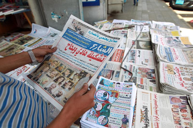 A Yemeni man reads a daily newspaper headline announcing that President Abdrabuh Mansur Hadi named former oil minister Khalid Bahah as the country's new premier, November 8, 2014, in Sanaa (AFP Photo/Mohammed Huwais)