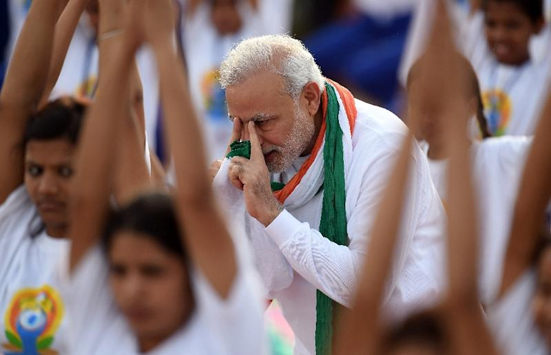 Indian Prime Minister Narendra Modi (C) gives instructions as yoga practitioners take part in a mass yoga session to mark International Yoga Day on Rajpath in New Delhi on June 21, 2015 (AFP Photo/Prakash Singh)