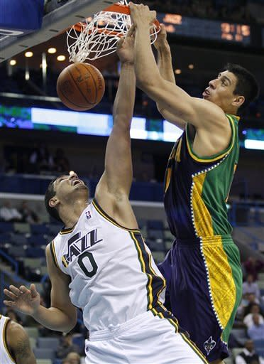 New Orleans Hornets power forward Gustavo Ayon (15) dunks over Utah Jazz forward DeMarre Carroll (0) in the second half of an NBA basketball game in New Orleans, Monday, Feb. 13, 2012. The Hornets won their fifth game this season 86-80.(AP Photo/Jonathan Bachman)