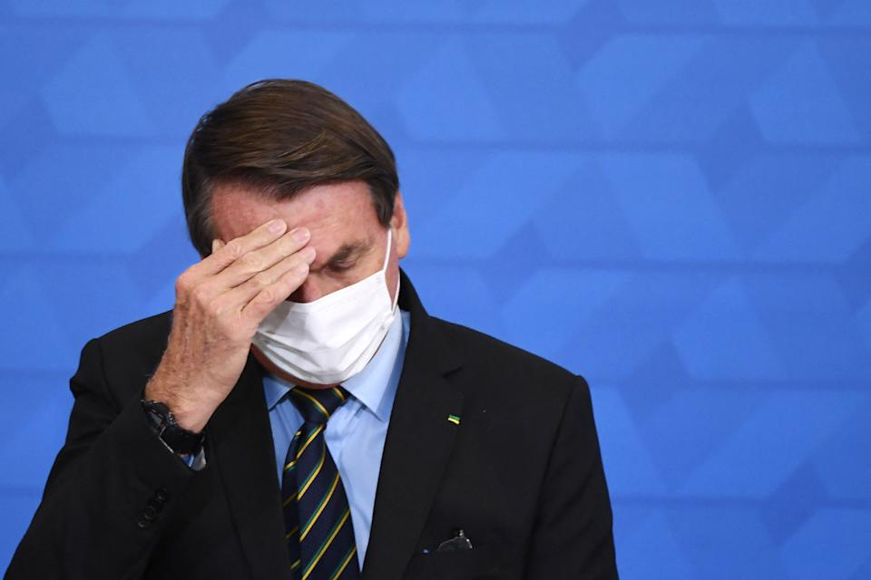 TOPSHOT - Brazilian President Jair Bolsonaro gestures as he speaks during the announcement of support measures to philanthropic hospitals in the fight against the novel coronavirus disease, COVID-19, at Planalto Palace in Brasilia, on March 25, 2021. - Brazil's death toll in the coronavirus pandemic surpassed 300,000 on March 24, as a deadly surge that has pushed hospitals to the brink made it the second country after the United States to pass the bleak milestone. (Photo by EVARISTO SA / AFP) (Photo by EVARISTO SA/AFP via Getty Images)