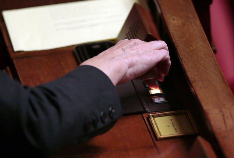 A member of parliament votes during a debate on legalising same-sex marriage at the National Assembly on January 29, 2013 in Paris. Deputies voted 249-97 in favour of Article One of the draft law, which redefines marriage as being a contract between two people rather than necessarily between a man and a woman